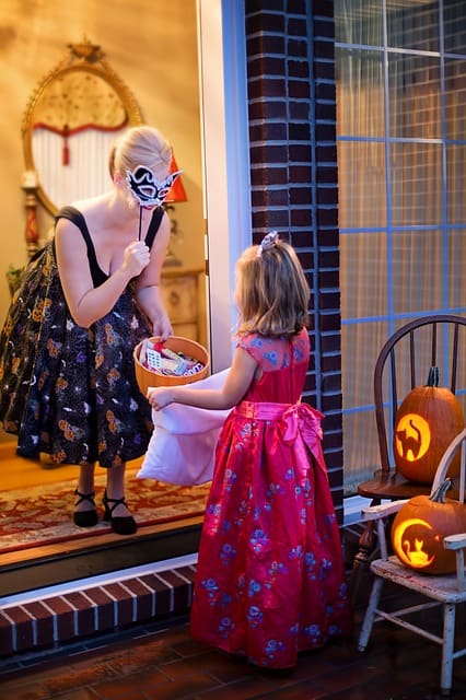 Young trick-or-treater getting candy from masquerade woman