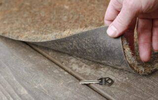 house key under corner of door mat