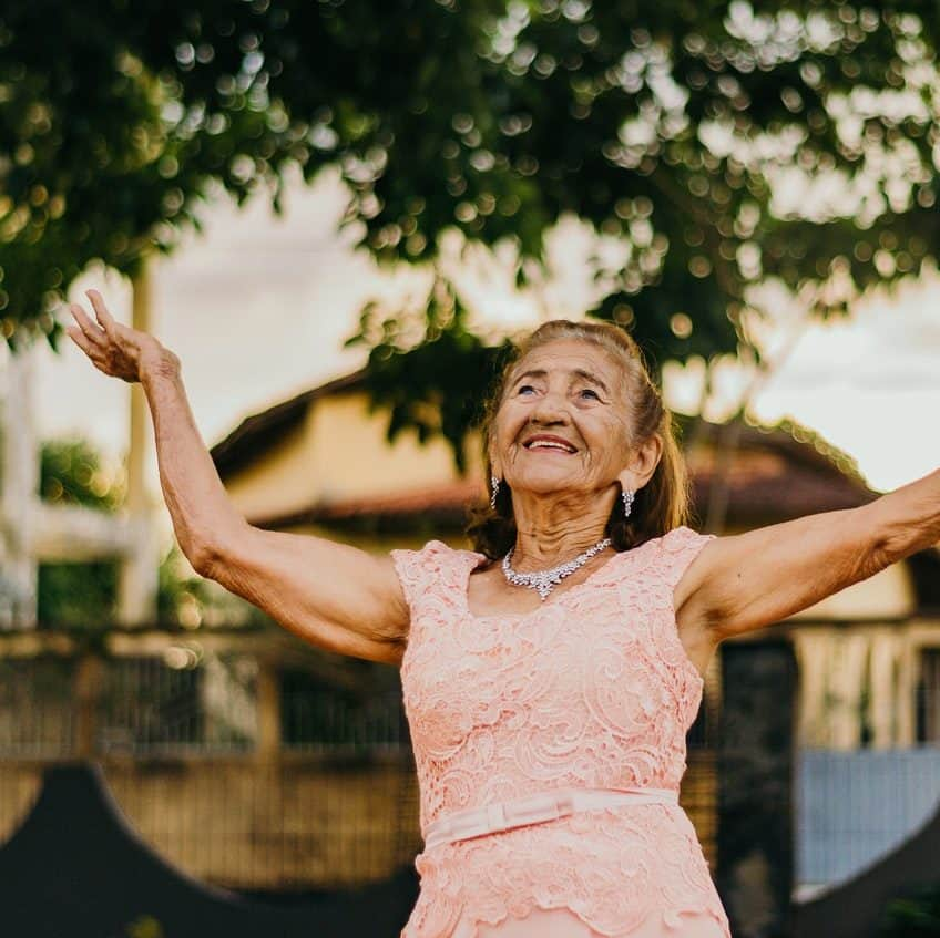 older woman in pink dress dancing with her arms in the air