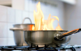 flaming frying pan on the stove top