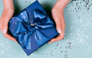 caucasian hands holding a blue wrapped present