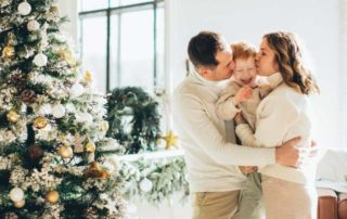 a man woman and child embracing by their christmas tree